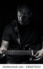 one man, playing guitar, dark and moody rock musician. Dark and moody atmosphere and lights. Shot on black background behind. black and white image.
