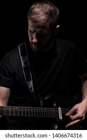 one man, playing guitar, dark and moody rock musician. Dark and moody atmosphere and lights. Shot on black background behind.