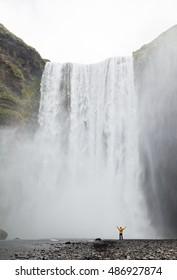 One man posing at Skogafoss waterfall in Iceland