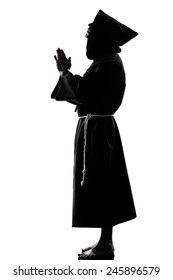 one  man priest praying silhouette in studio isolated on white background
