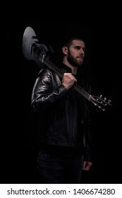 one man, rock or metal musician holding a guitar posing. Black background behind. Moody and dark atmosphere.