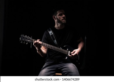 one man, rock or metal musician, barely recognizable person, playing a guitar. Black background behind.