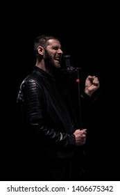 One man, rock or metal musician singing on a microphone. Shot on a black background. Dark and moody atmosphere.