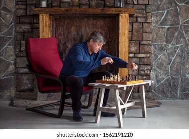One man sits on chair in country house and plays chess with himself. Waiting and loneliness. General plan