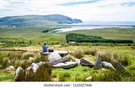 One man sitting on top of the Neolithic, Megalithic Tomb on Slievermore on Achill Island along the Wild Atlantic Way in Ireland in summer.