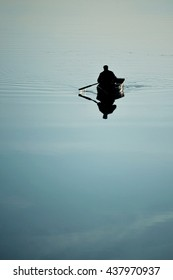 one man in a small boat sailing boat on the lake river rowing oars. River with a smooth mirror surface of the water. Weather quiet, calm, windless