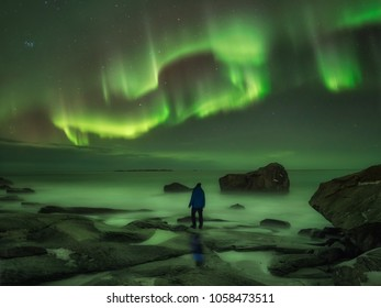one man standing at the beach watching the northern lights dancing in the sky, surreal dark scene, solitude concept, rocks in the water and green reflection