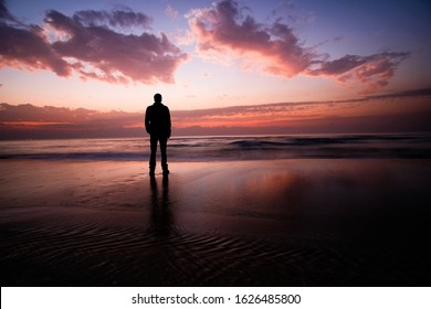 one man standing on the beach and looking at the sunset over over the waves and the sea. the clouds are in the sky above.