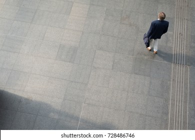 One man stands alone in a metro station, view from above.  Man carries a briefcase and wears a sports coat, khaki trousers. Man traveling for business through a European train station, bird's eye view