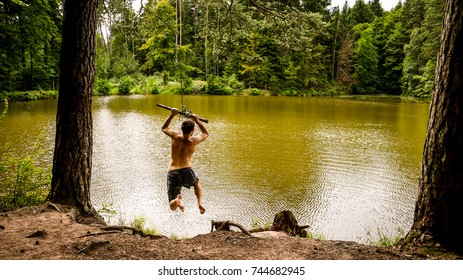 One man swinging from a rope into a forest lake on a cloudy day. Taken in Dentlein Am Forst, in Bavaria, Germany.