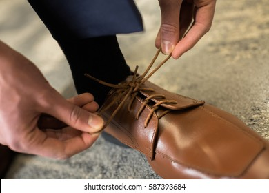One man ties formal brown dress shoes as he gets dressed for prom. Pulling knot in shoestrings dress shoes.