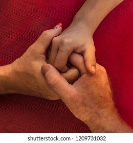 One man and two women holding hands on a table implying a polyamory relationship or love triangle.