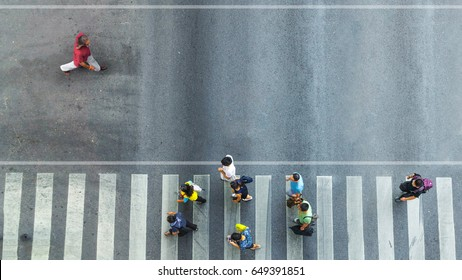 the one man walk converse,  the busy city crowd move to pedestrian crosswalk on businees traffric road (Aerial photo, top view)