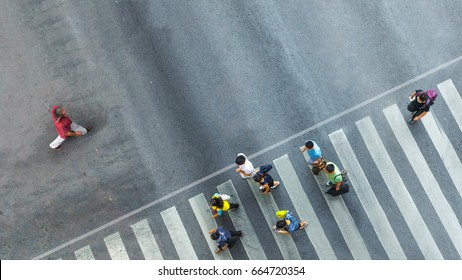the one man walk converse,  the busy city crowd move to pedestrian crosswalk on business traffic road (Aerial photo, top view)