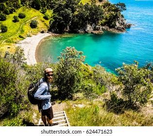One man walking along the Owhanake coastal track on Waiheke Island, with ocean and bush in the background.