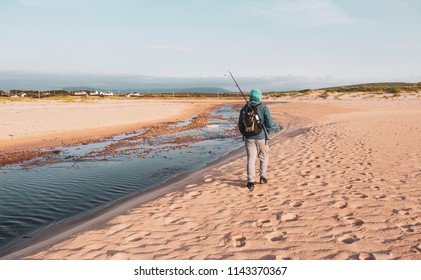 One man walking to go fishing at the beach with a backpack and a fishing rod , wearing a hoodie. Taken in Golden Strand in Achill Island, Ireland