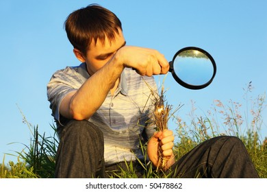 one man wearing shirt and jeans with magnifier is sitting on a meadow and burning grasses