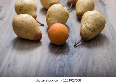 one mandarin among pears on a wooden table