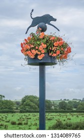 One of the many landmark posts of boar pig in St Clears, Carmarthenshire, sitting atop of peach coloured begonia flowers,