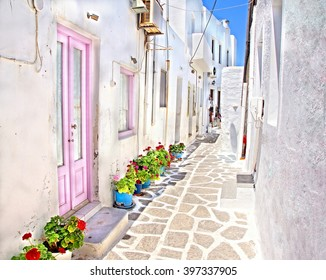 One of the many white washed picturesque sunny cobble stone streets at the Cyclades  Island of Mykonos, Greece