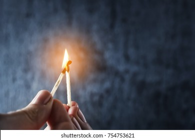 One match sets the other on fire. Fire from matches on a dark blue background. The concept of support, leadership. Photo with copy space.
