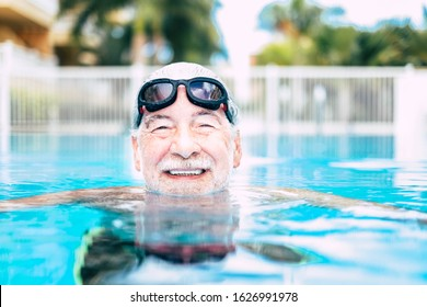 one mature man or senior at the swimming pool looking at the camera smiling and having fun alone - healthy and fitness lifestyle