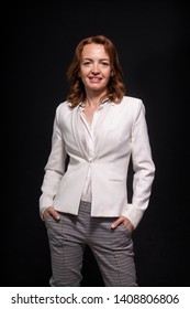 One mature woman, 40 years old, businesswoman portrait casual posing, standing. Black background behind.
