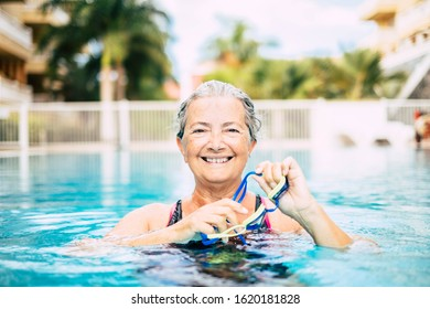 one mature woman doing activity at the pool swimming and training alone - looking at the camera ad smiling