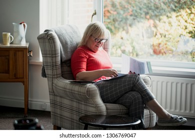 One mature woman is sitting in an armchair in the living room of her home, reading through letters.