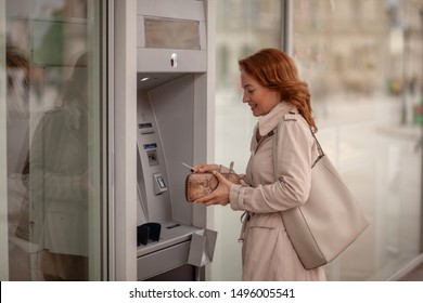One mature woman, using ATM machine, putting her credit card in a wallet.