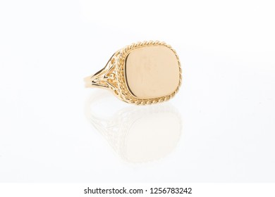 One men's gold bezel ring with plain shiny flat golden surface on white background with reflection
