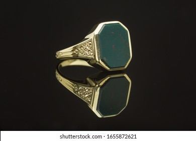 One mens gold and bloodstone heliotrope ring on black reflective background closeup