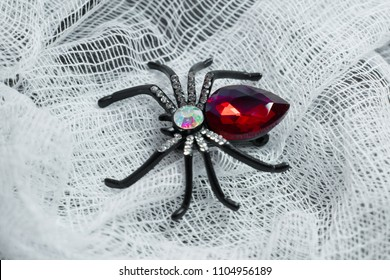 One metal brooch in the form of a spider, large, black with ornament and red ruby stone on a white medical bandage, textured background, symbolizes the bite and danger of insects during the high seaso