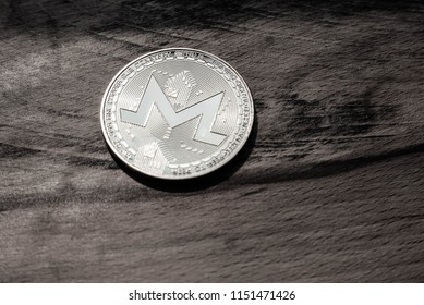 One Monero coin on a background of grained wood.
