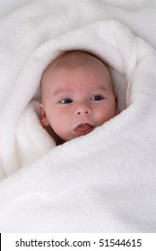 one month old baby wrapped in a white towel
