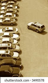 one more parking space left in a crowded stuffed lot of cars in the urban city setting