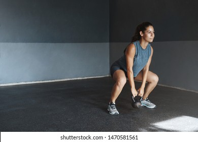 One more sit-up to achieve goal. Good-looking motivated hispanic sportswoman wear activewear, look determined hold kettlebell, make fitness crossfit exercise, perform squats stand gym