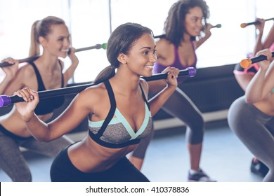 One more squat. Beautiful young women with perfect bodies in sportswear exercising with barre while standing in front of window at gym
