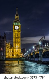 One of the most iconic landmarks of London, Big Ben at the summit of the Elizabeth Tower right above the clock face, seen at night in front of the very famous Thames river.