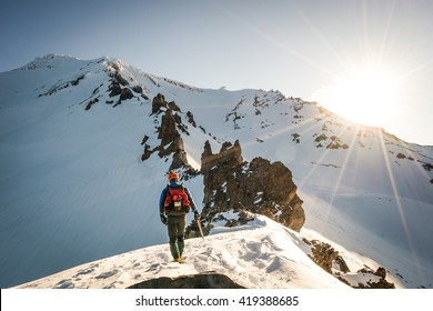 One mountaineer climbs rocky, snowy mountain at dawn.
