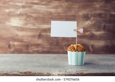 One muffin with streusel on the wooden table with the white paper for text. selective focus