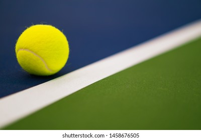one new tennis ball near white line in blue and green hard court with copy space on right
