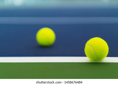 one new tennis ball on white line in blue and green hard court with blurred ball on left