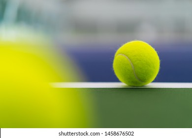 one new tennis ball on white line in blue and green hard court with blurred ball on left foreground