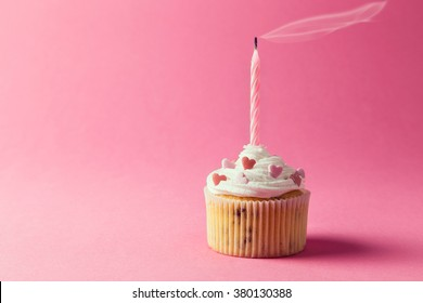One nicely decorated muffin with cream, sprinkles and birthday candle isolated on pink background