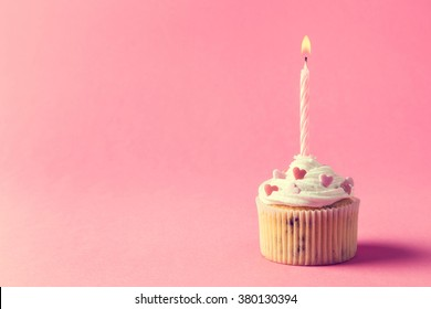One nicely decorated muffin with cream, sprinkles and lighted birthday candle isolated on pink background