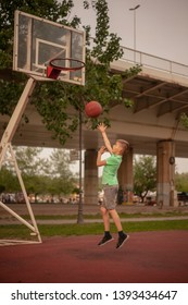 one nine year old boy, shooting ball up to a backboard, ball flying in mid air. playing basketball alone on Spring day outdoors.