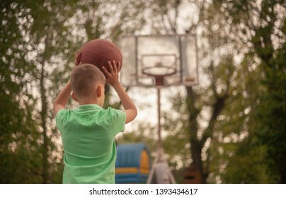 One nine years old boy, rear view from behind, holding a ball in his hands, raising it up to shoot. On a Spring day, at a basketball court outdoors.