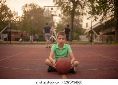 one nine years old boy, sitting on basketball court, on a beautiful Spring day. people playing in background.