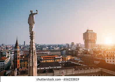 One of numerous statues of main Cathedral in Milan looks on modern city